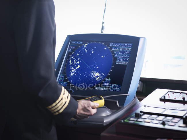Ship's captain working on bridge with radar screen, close up — Stock Photo