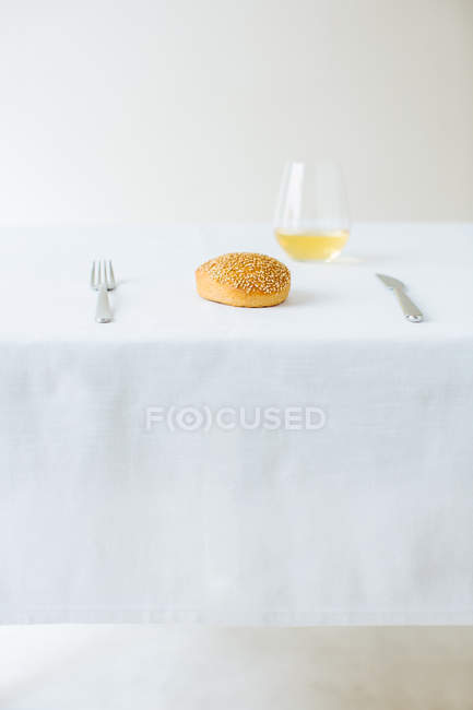 Table setting with simple seeded roll and white wine — Stock Photo