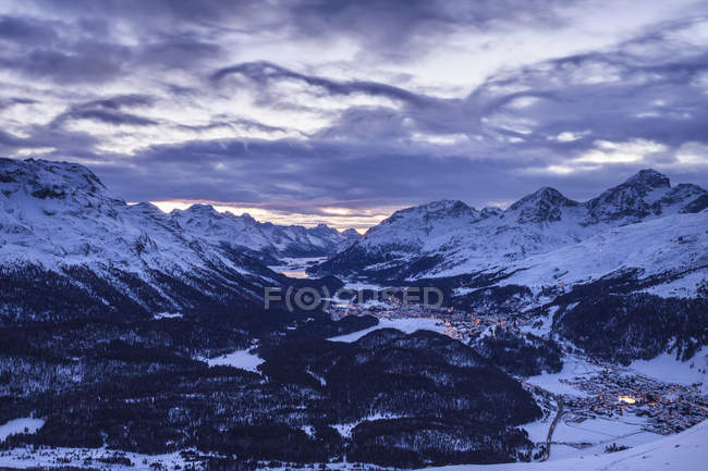 Snowcapped rocky mountains under cloudy sky at dusk — Stock Photo