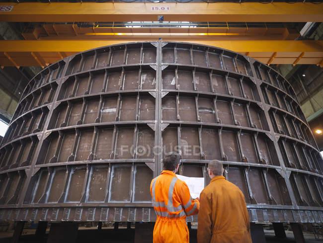 Інженери оглядають конструкцію морського виробництва — стокове фото