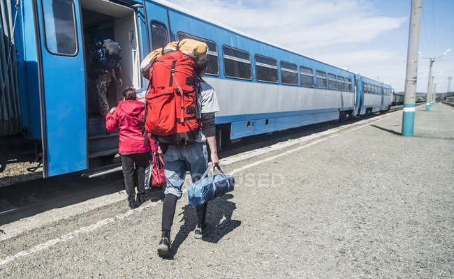 Rear view of young hikers with backpacks boarding a train — Stock Photo