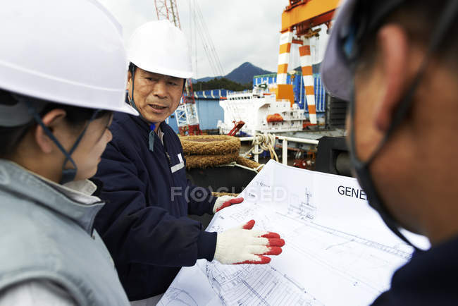 Workers looking at plans at shipyard, GoSeong-gun, South Korea — Stock Photo