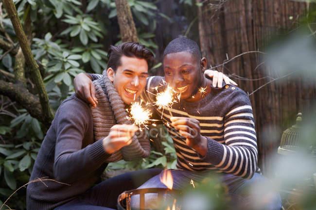 Deux jeunes hommes accroupis devant le feu de jardin avec des étincelles — Photo de stock