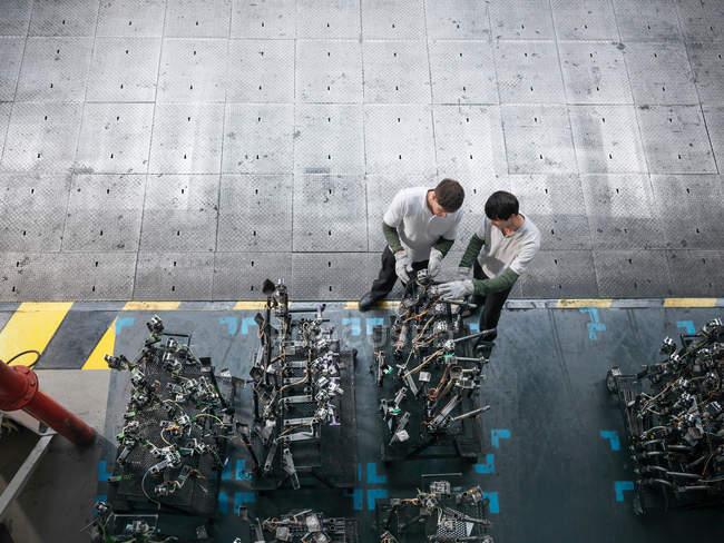 Vue grand angle des ingénieurs inspectant les pièces de presse dans l'usine automobile — Photo de stock