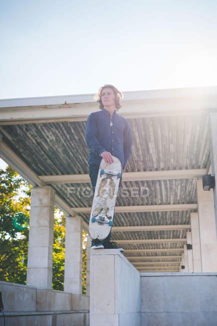 Retrato de un joven skater urbano de pie en la pared con monopatín - foto de stock
