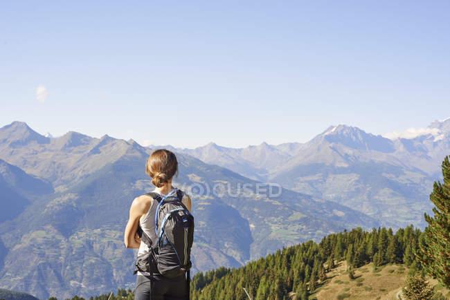 Veduta posteriore dell'escursionista che si affaccia sul paesaggio montano, Valle d'Aosta, Aosta, Italia — Foto stock
