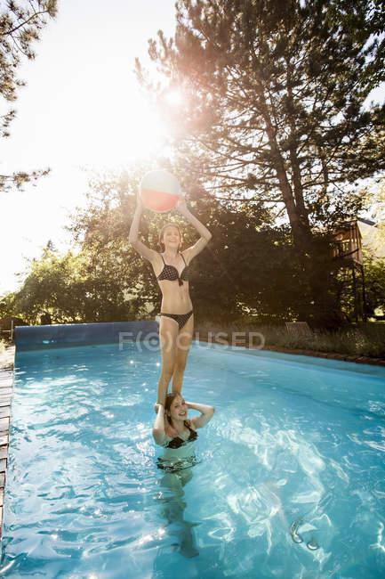 Teenage girl standing on best friends shoulders in swimming pool — Stock Photo