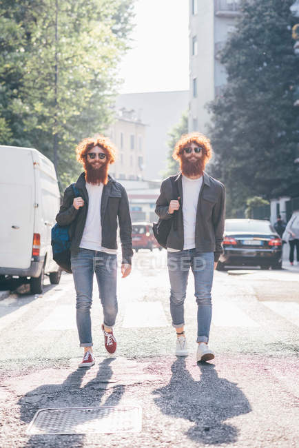 Young male hipster twins with red hair and beards strolling on city road — Stock Photo