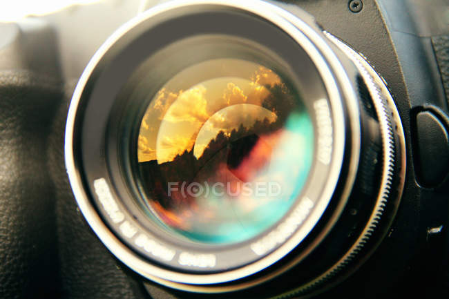 Sunset clouds reflected in camera lens, close up shot — Stock Photo