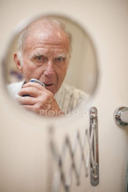 Portrait of senior man in shaving mirror using electric razor — Photo de stock