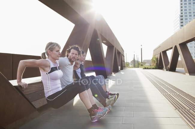 Две женщины и мужчина натолкнулись на городской пешеходный мост — стоковое фото