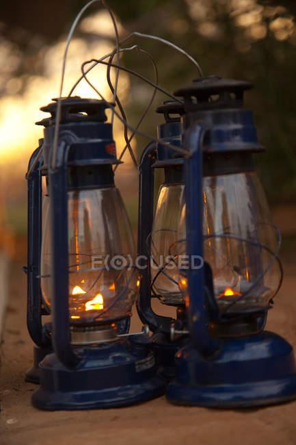 Tres linternas retro en la arena, de cerca - foto de stock