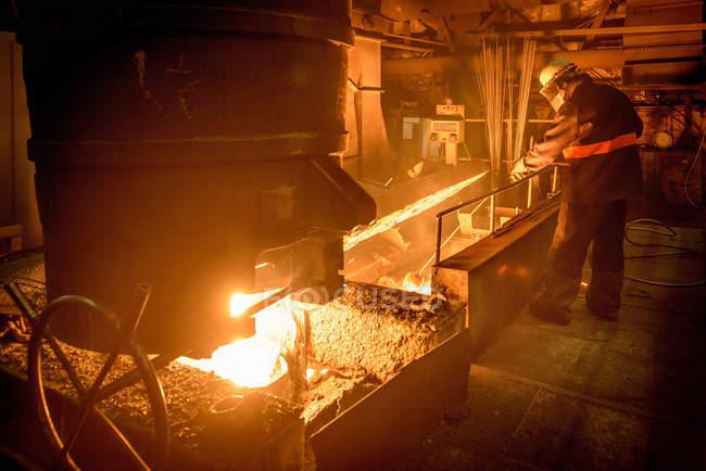 Лицо в защитной одежде, работающее с расплавленной сталью, когда она заливается в промышленный литейный цех — стоковое фото