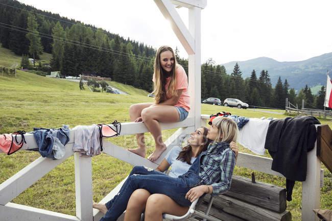 Троє дорослих друзів, які сидять на ганку, Sattelbergalm, Тіроль, Австрія — стокове фото