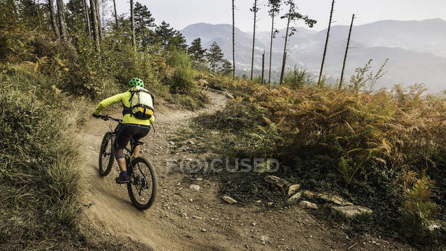 Mid adult woman cycling up dirt track, Finale Ligure, Savona, Italy — Stock Photo