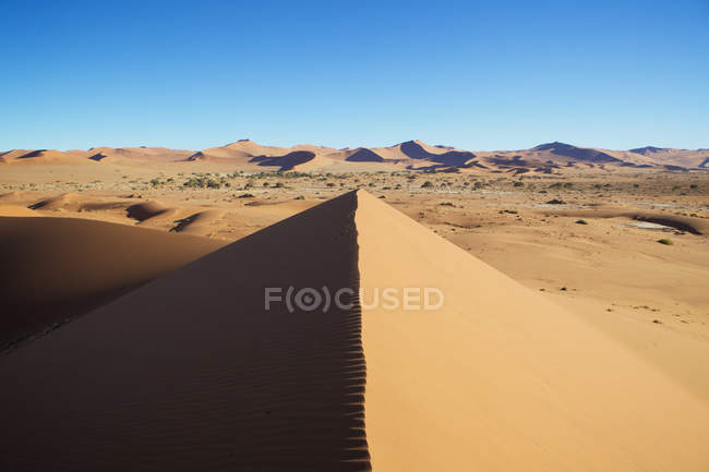 Large sand dune in bright sunlight with clear sky — Stock Photo