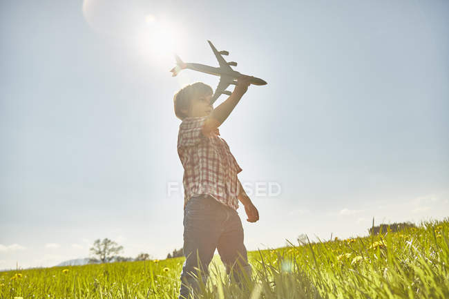 Хлопчик в сонячної поля з синього неба, граючи з іграшкою літак — стокове фото