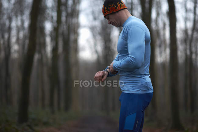 Бегун носить вязать шляпу и спандекс глядя на наручные часы — стоковое фото