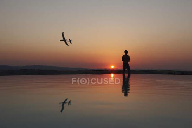 Силуэт человека, летающего радиоуправляемым самолетом на побережье заката, Буонконвенто, Тоскана, Италия — стоковое фото