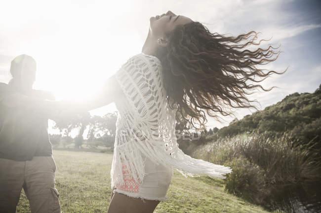 Молодая пара в солнечном свете, взявшись за руки, бросая голову назад усмехнуться — стоковое фото