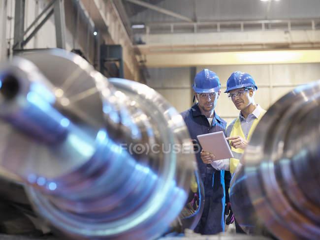 Ingénieurs inspectant les rouleaux en acier finis dans l'usine d'ingénierie — Photo de stock
