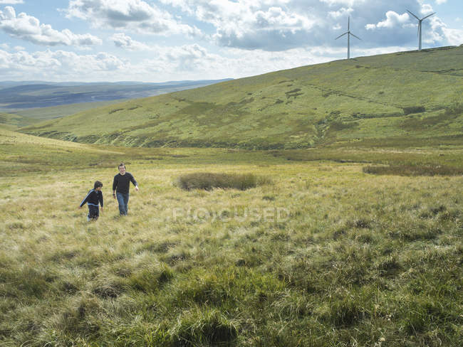 Brothers walk up hill together at windfarm — Stock Photo