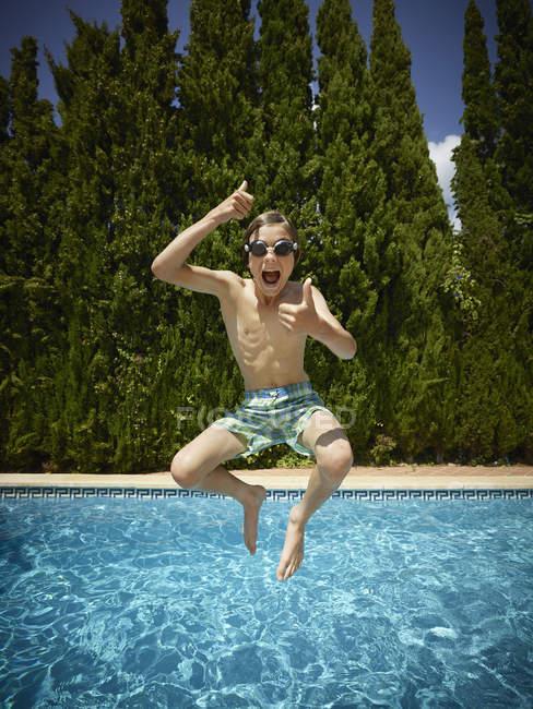Мальчик прыгает в бассейн, Мальорка, Испания — стоковое фото