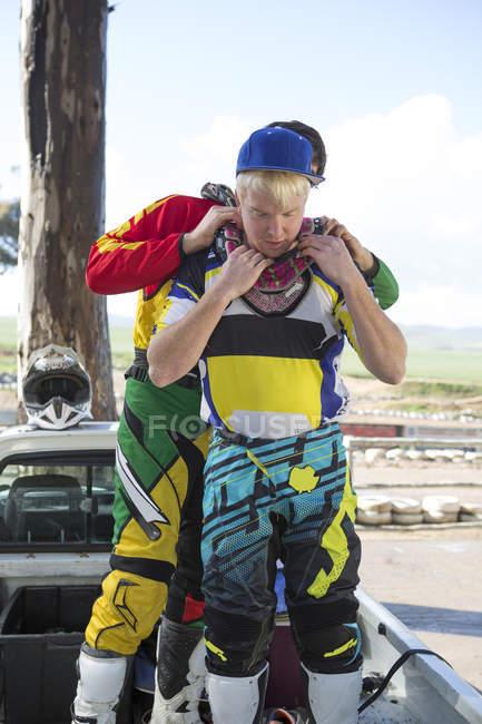 Zwei junge männliche Motocross-Fahrer bereiten sich auf das Rennen vor — Stockfoto