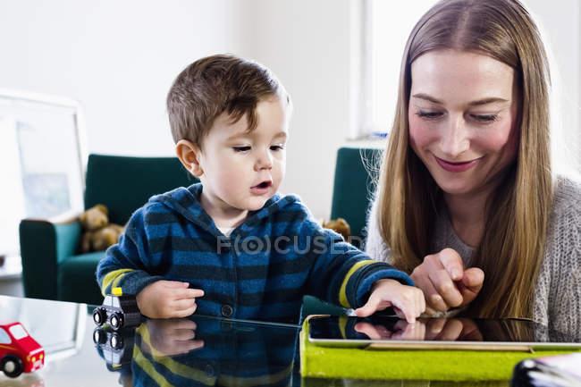 Середині жінки дорослого і дитину сина, використовуючи сенсорний цифровий планшет за столом — стокове фото