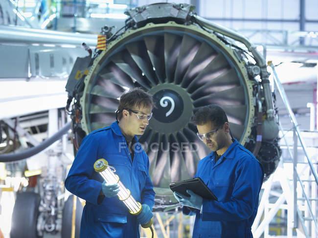 Ingenieros de aeronaves discutiendo detalles de mantenimiento en tableta digital delante del motor a reacción en fábrica de mantenimiento de aeronaves - foto de stock