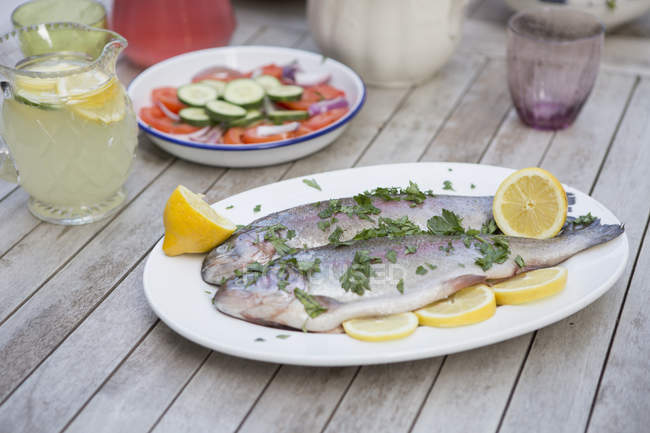 Raw trouts with herbs and lemon slices on plate — Stock Photo
