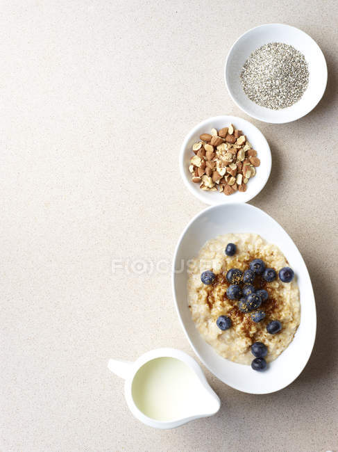Still life of porridge with fruit and nuts — Stock Photo