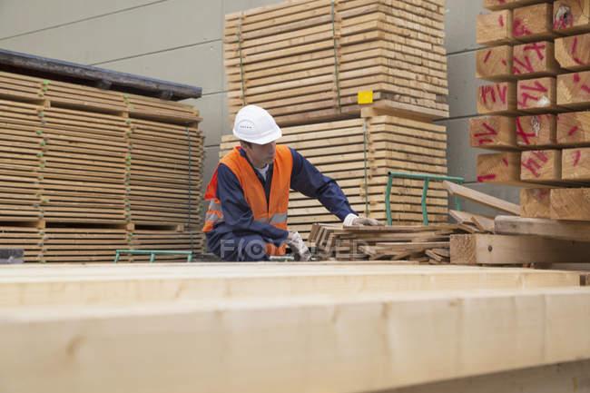Столяр, сортировка деревянные доски древесины дворе — стоковое фото