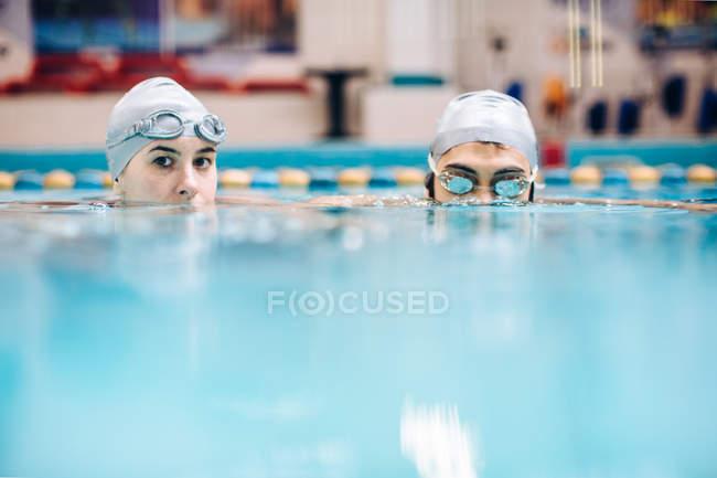 Пара в басейн, носіння плавальний caps визирав з води — стокове фото