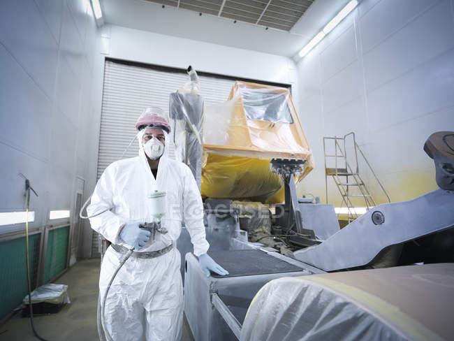 Retrato del técnico de pulverización de pintura en la fábrica de reparación de camiones - foto de stock