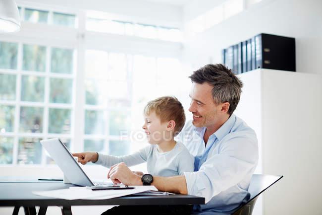 Homme avec le fils utilisant l'ordinateur portatif au salon — Photo de stock