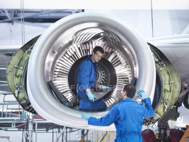 Инженеры, работающие с турбиной реактивного двигателя на авиаремонтном заводе — стоковое фото