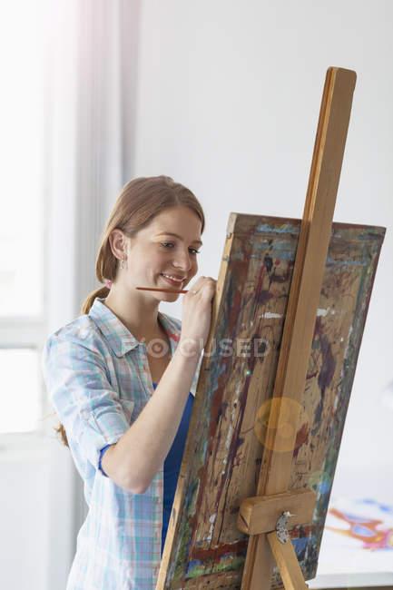 Жіночий художник живопис на станковий в приміщенні — стокове фото