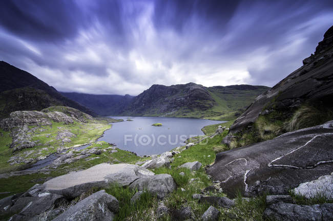 Lake surrounded by green hills under cloudy sky — Stock Photo