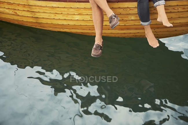Feet of middle aged couple sitting on boat over water — Stock Photo