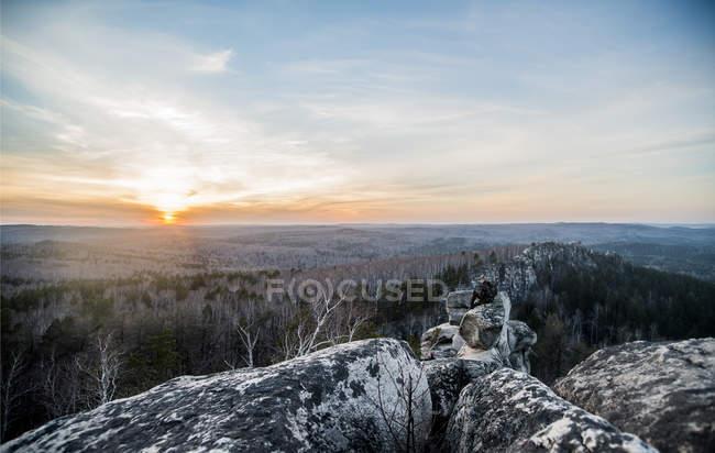 Jeune mâle randonneur sur le dessus de la formation rocheuse au coucher du soleil — Photo de stock