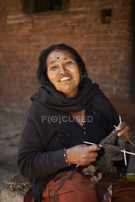 Portrait of female trader knitting on street, Thamel, Kathmandu, Nepal — стокове фото