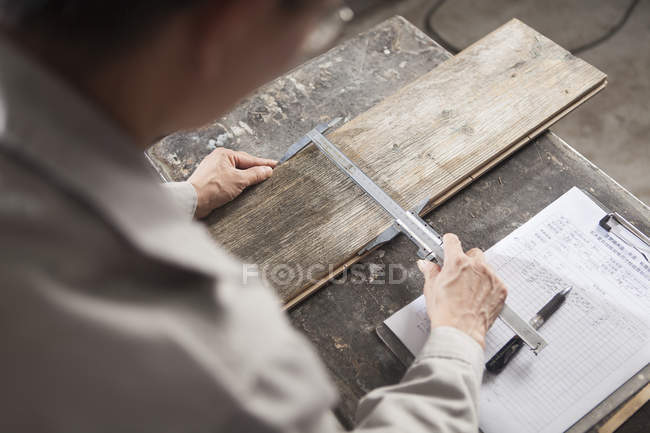Carpenter measuring wood plank with vernier caliper in factory — Stock Photo