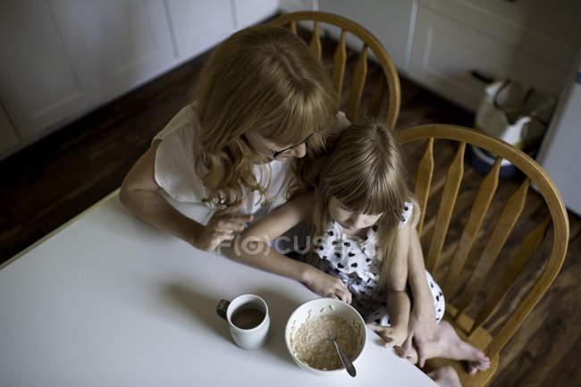 Mutter und Tochter kuscheln am Frühstückstisch — Stockfoto