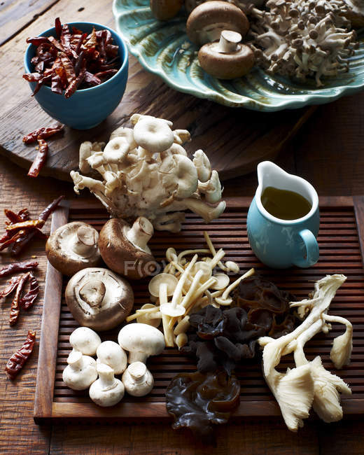 Various mushrooms on wooden board and dried chillis in bowl — Stock Photo