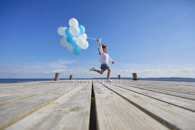 Jeune fille courant sur une jetée en bois, tenant un tas de ballons — Photo de stock
