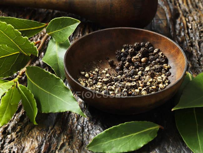 Granos de pimienta triturados en cuenco y hojas de laurel en la superficie de madera rústica - foto de stock