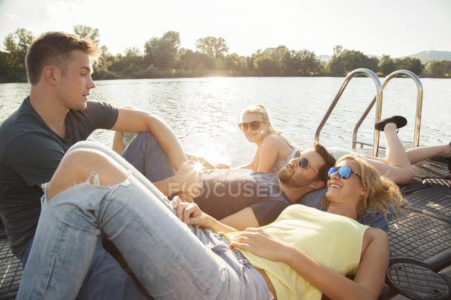 Cuatro amigos adultos jóvenes charlando en el muelle de la orilla del río - foto de stock