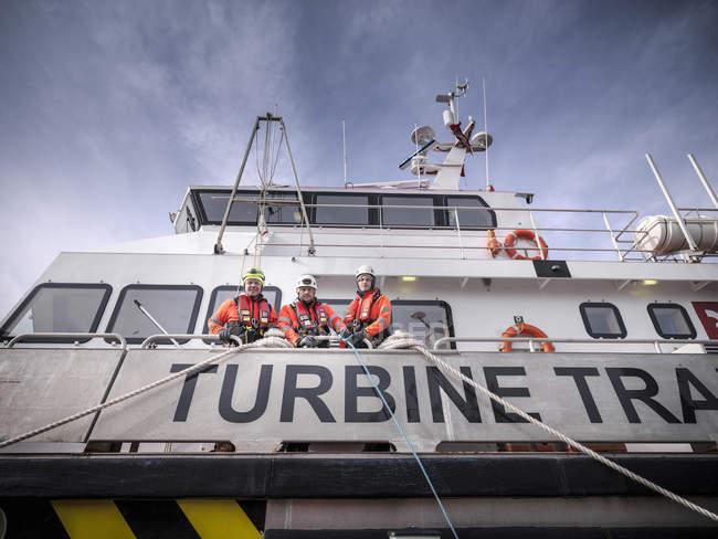 Retrato de coordenadores offshore do parque eólico na porta no navio — Fotografia de Stock