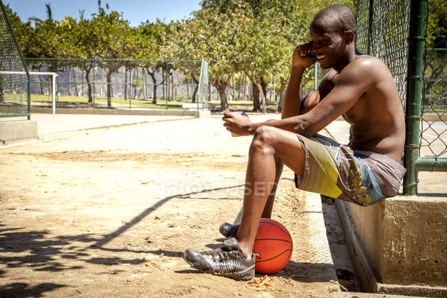 Молодой баскетболист болтает на смартфоне и пьет воду — стоковое фото